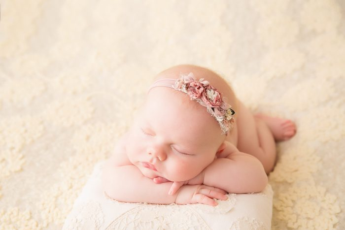 Newborn laying on fur rug on stomach with chin on top of arms crossed wearing floral headband