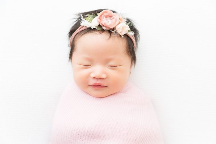 Newborn wrapped in pink blanket wearing pink floral head band