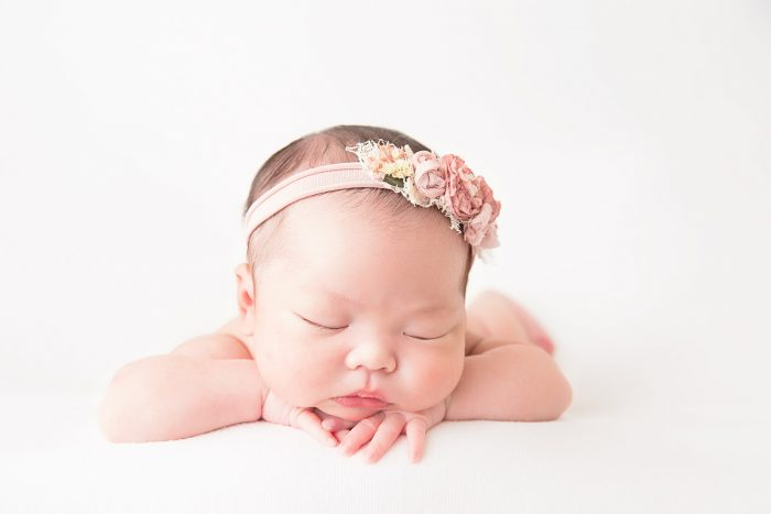 Newborn laying on stomach with chin on top of crossed hands wearing floral headband