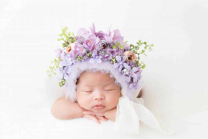 Newborn Girl wearing a floral bonnet laying on her stomach on a white blanket