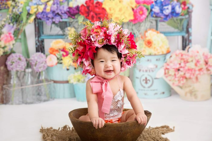 Baby sitting in large wooden bowl wearing pink ribbon around neck and floral head piece