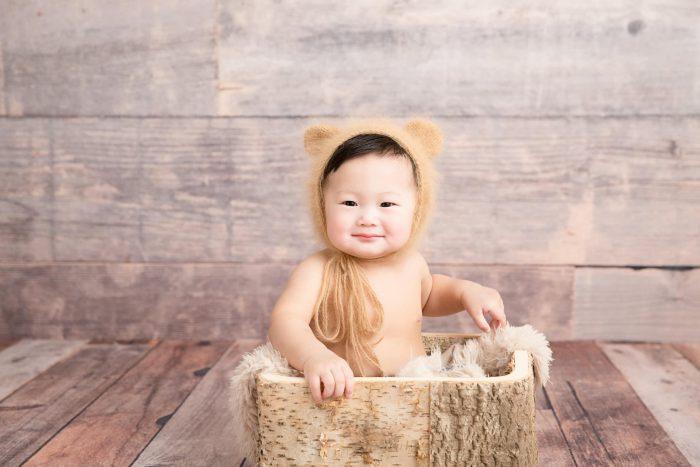 Baby siting in basket wearing teddy bear ears head cap