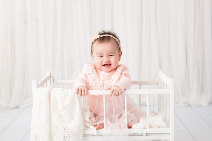 Baby standing in crib wearing pink dress and pink floral head piece