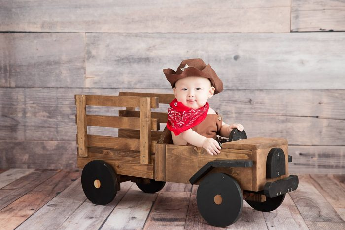 Baby wearing cowboy outfit and cowboy hat sitting in wooden wagon