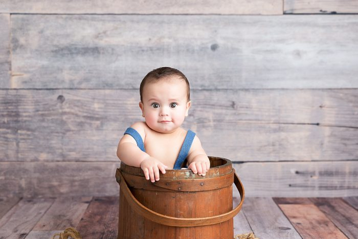 Baby posing standing in wooden bucket